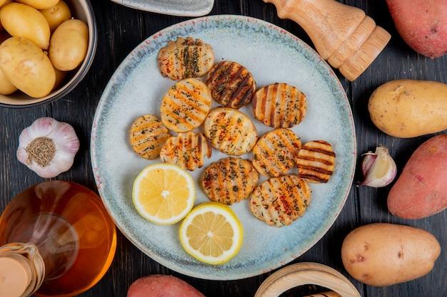 Bovenaanzicht van gebakken gegolfde aardappelschijfjes en schijfjes citroen in plaat met hele boterknoflook op houten oppervlak