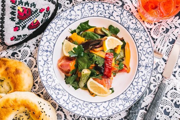 Bovenaanzicht van gebakken groenten salade met paprika aubergine tomatenkruiden en citroen
