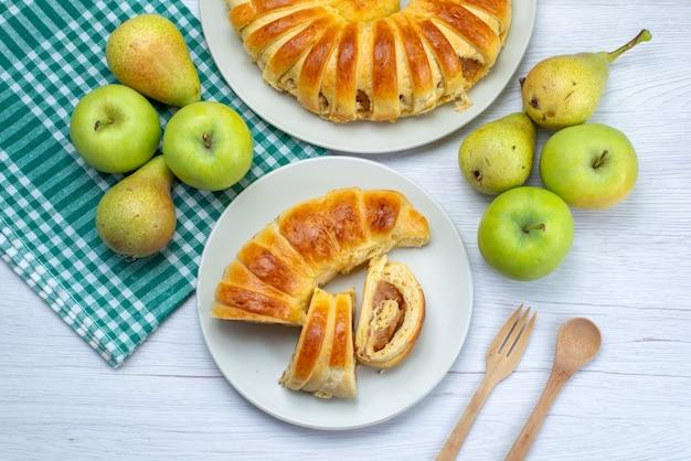 Bovenaanzicht van gebakken heerlijk gebak armband gevormd in glazen plaat samen met appels en peren op wit, gebak biscuit zoete bak thee fruit