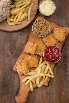Bovenaanzicht van gebakken kip met frietjes en verschillende soorten saus