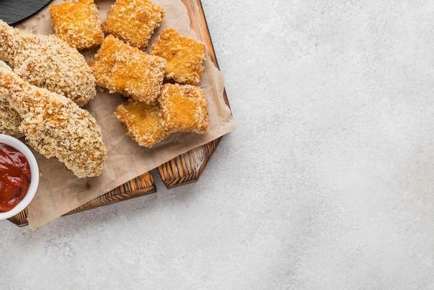 Bovenaanzicht van gebakken kip met nuggets en kopie ruimte