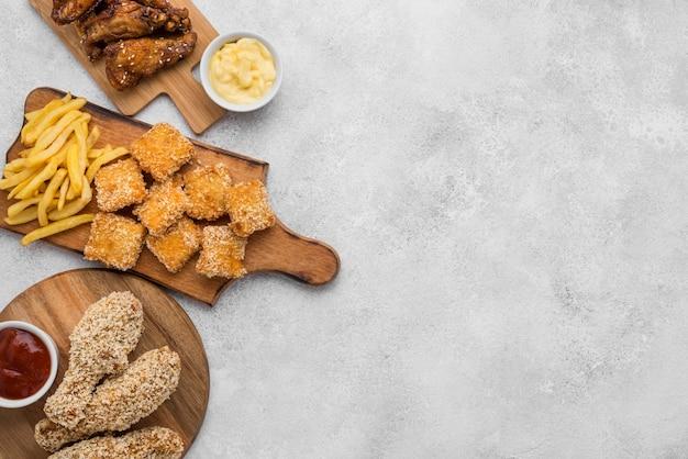 Bovenaanzicht van gebakken kip met sauzen en nuggets op snijplanken met kopie ruimte