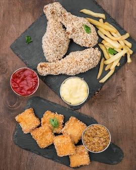 Bovenaanzicht van gebakken kip met verschillende soorten saus en frietjes