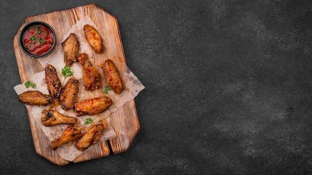 Bovenaanzicht van gebakken kipdelen met saus en kopieer de ruimte
