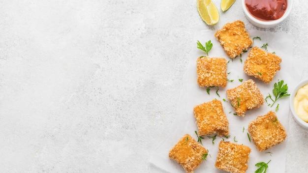 Bovenaanzicht van gebakken kipnuggets met sauzen en kopie ruimte