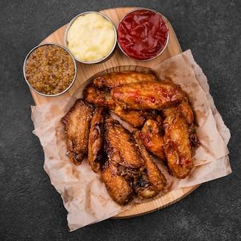 Bovenaanzicht van gebakken kippenvleugels met verschillende sauzen