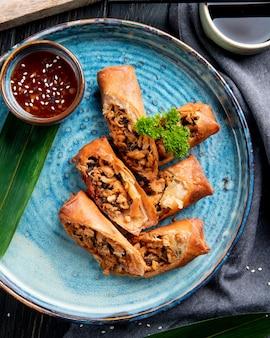 Bovenaanzicht van gebakken loempia's met kip en groenten geserveerd met sojasaus op een plaat op zwart