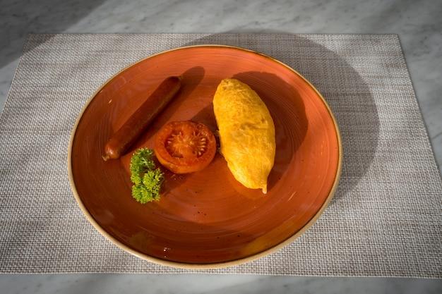 Bovenaanzicht van gebakken omelet met geroosterde worst en gesneden tomaat op tafel met ochtendlicht, zelfgemaakt ontbijt