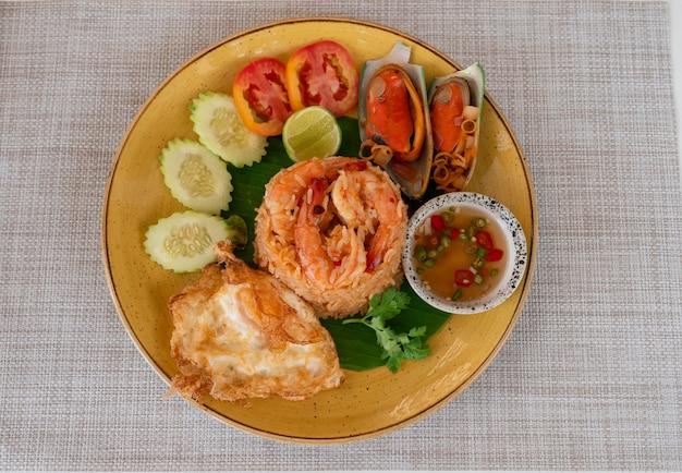 Bovenaanzicht van gebakken rijst met zeevruchten en thaise traditionele pittige en zure saus (tom yum) met kruiden op tafel