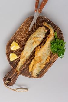 Bovenaanzicht van gebakken vis navaga geserveerd op houten snijplank met citroen, groenten en greens op grijze achtergrond.