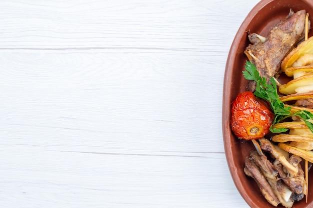 Bovenaanzicht van gebakken vlees met groenen en gebakken pruimen binnen bruine plaat op licht bureau, voedsel maaltijd vleesgerecht diner