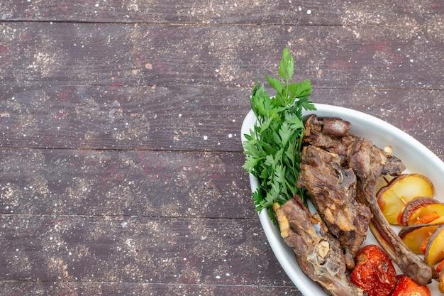 Bovenaanzicht van gebakken vlees met groenen en gebakken pruimen in plaat op bruin houten bureau, voedsel maaltijd vleesgerecht diner