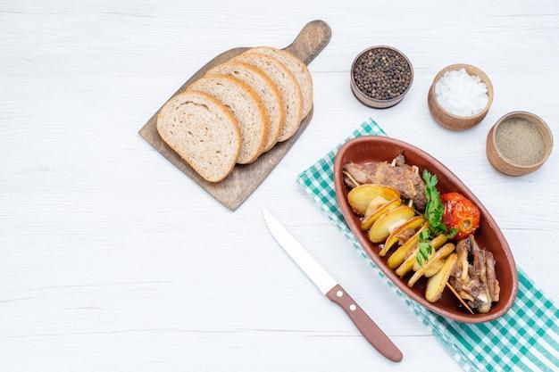 Bovenaanzicht van gebakken vlees met groenten en gebakken pruimen in plaat met broodbroodjes zout op licht bureau, voedsel maaltijd vleesgerecht diner