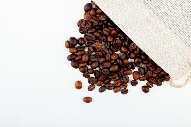 Bovenaanzicht van gebrande koffiebonen verspreid uit een zak op witte achtergrond met kopie ruimte