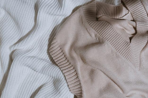 Bovenaanzicht van gebreide katoenen witte trui en beige mouwloze top