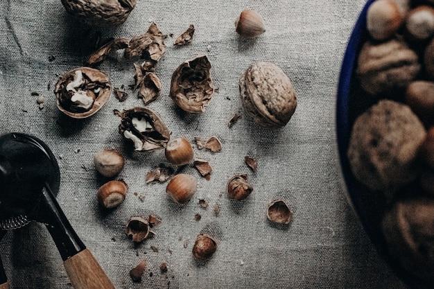 Bovenaanzicht van gebroken walnoten met hazelnoten en een breker op een stoffen oppervlak