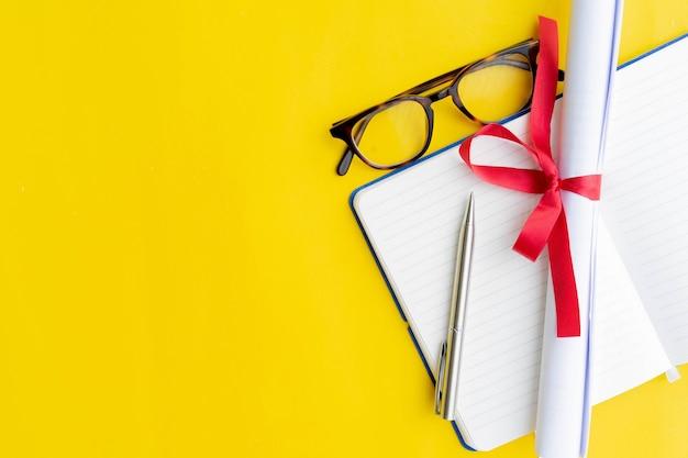 Bovenaanzicht van gediplomeerd diploma met notitieboekje en pen en bril op gele achtergrond
