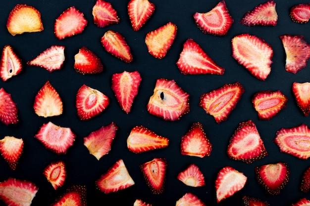 Bovenaanzicht van gedroogde aardbeien plakjes geïsoleerd op zwarte achtergrond