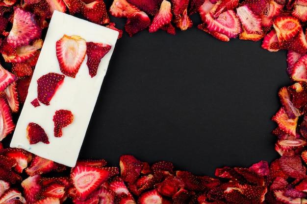 Bovenaanzicht van gedroogde aardbeien segmenten met witte chocoladereep op zwarte achtergrond