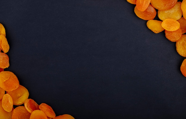 Bovenaanzicht van gedroogde abrikozen op zwarte achtergrond met kopie ruimte