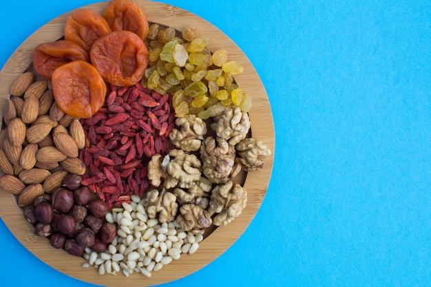 Bovenaanzicht van gedroogde abrikozen, rozijnen, gojibessen, verschillende noten op de ronde snijplank op blauw