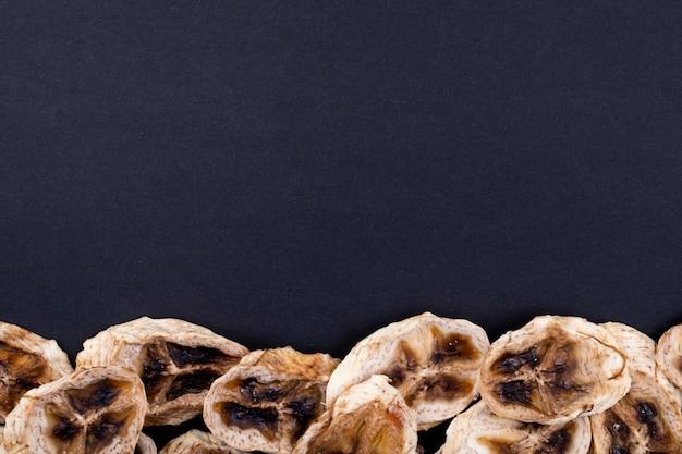 Bovenaanzicht van gedroogde bananenchips gerangschikt aan de onderkant op zwarte achtergrond met kopie ruimte