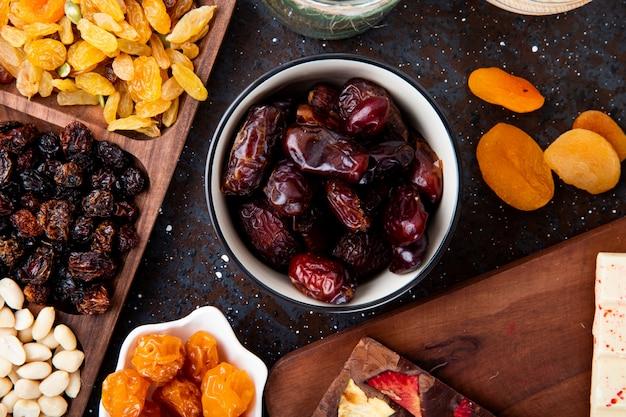 Bovenaanzicht van gedroogde dadels in een kom met gedroogde kersen pruimen en abrikozen op zwart