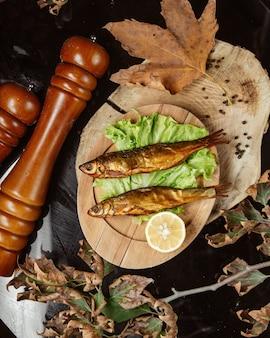 Bovenaanzicht van gedroogde gerookte vis geserveerd met citroen op houten schotel