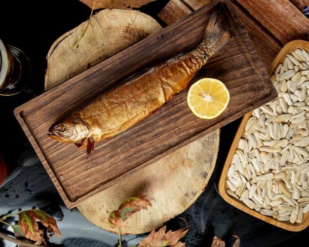 Bovenaanzicht van gedroogde gerookte vis geserveerd met halve citroen
