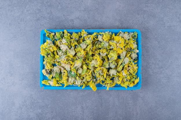 Bovenaanzicht van gedroogde gezonde bloem op blauwe houten plank.