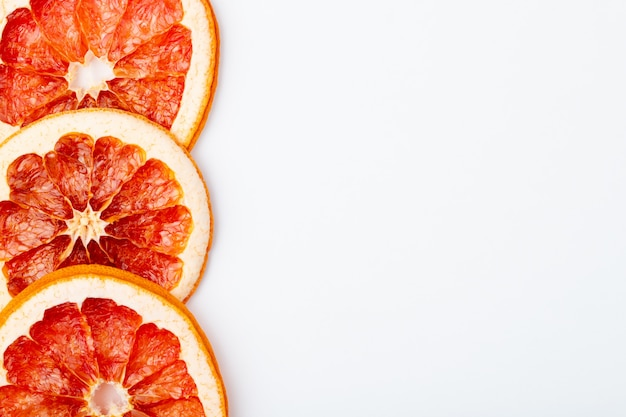 Bovenaanzicht van gedroogde grapefruit segmenten geïsoleerd op een witte achtergrond met kopie ruimte