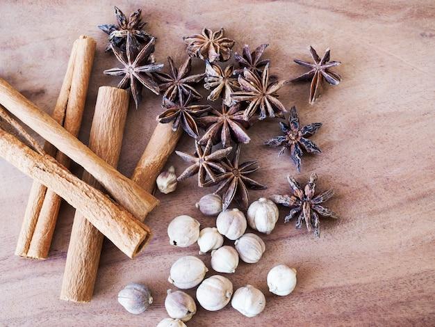 Bovenaanzicht van gedroogde kruiden en specerijen op bamboe geweven mand op houten tafel.