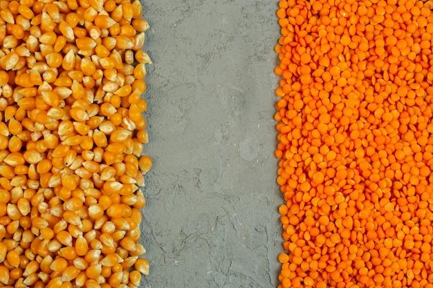 Bovenaanzicht van gedroogde maïs zaden en rode rauwe linzen met kopie ruimte op grijs