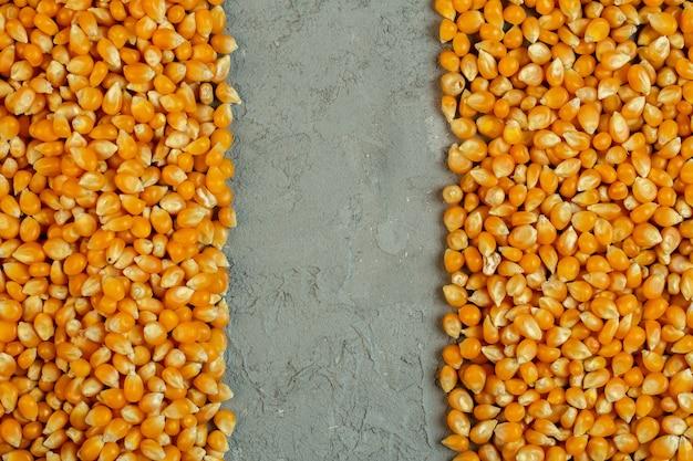 Bovenaanzicht van gedroogde maïs zaden met kopie ruimte in het midden op grijs