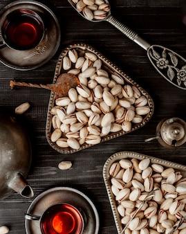 Bovenaanzicht van gedroogde pistaches in vintage metalen porties