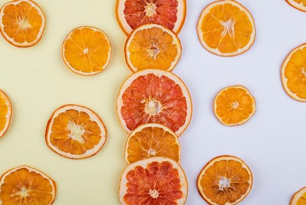 Bovenaanzicht van gedroogde plakjes sinaasappel en grapefruit gerangschikt op witte achtergrond