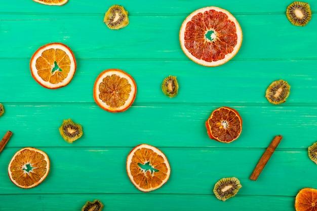Bovenaanzicht van gedroogde sinaasappel en grapefruit segmenten met gedroogde kiwi en kaneelstokjes op groene houten achtergrond