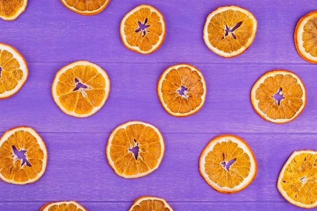 Bovenaanzicht van gedroogde stukjes sinaasappel geïsoleerd op paarse houten achtergrond