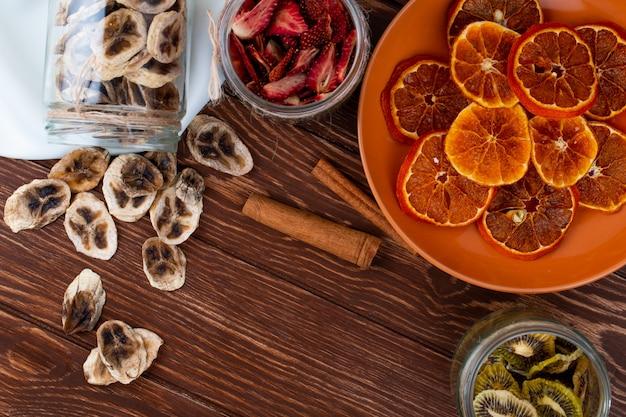 Bovenaanzicht van gedroogde stukjes sinaasappel in een plaat en verspreide gedroogde bananenchips uit een glazen pot met kaneelstokjes op houten achtergrond