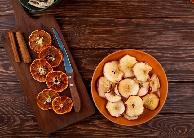 Bovenaanzicht van gedroogde stukjes sinaasappel met keukenmes op een houten snijplank en gedroogde appelschijfjes op een plaat op houten achtergrond