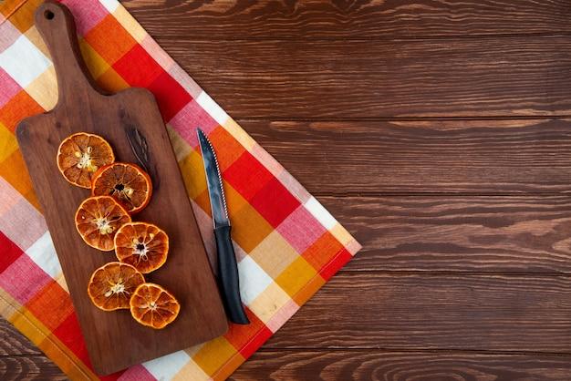 Bovenaanzicht van gedroogde stukjes sinaasappel met keukenmes op een houten snijplank op houten achtergrond met kopie ruimte