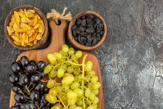 Bovenaanzicht van gedroogde vruchten druiven op het houten bord tussen twee kommen met gedroogde vruchten