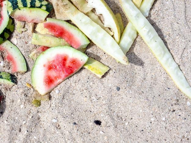Bovenaanzicht van gegeten watermeloen en meloenschillen op zand op zonnige zomerdag