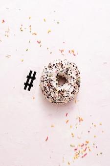 Bovenaanzicht van geglazuurde donut met hagelslag en hashtag symbool