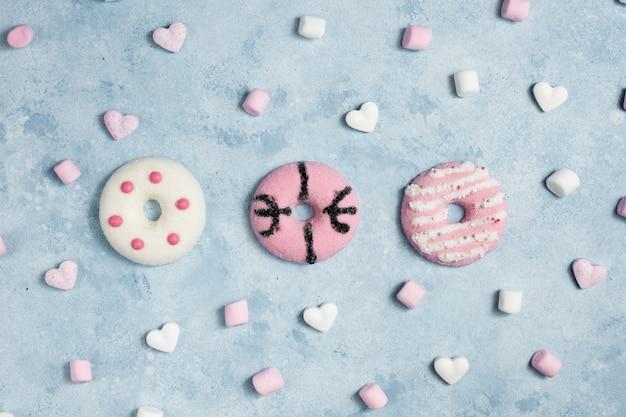 Bovenaanzicht van geglazuurde donuts met marshmallow en harten