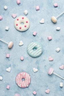 Bovenaanzicht van geglazuurde donuts met snoep en marshmallow