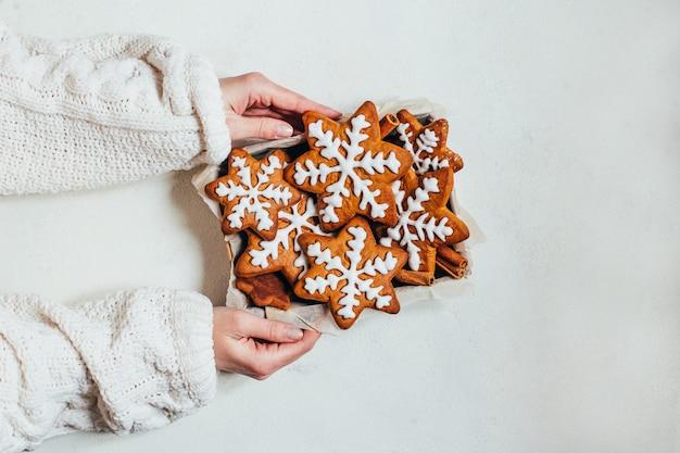 Bovenaanzicht van geglazuurde peperkoek kerstkoekjes in een doos in vrouwelijke handen op een witte achtergrond