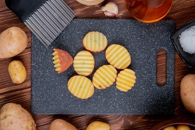 Bovenaanzicht van gegolfde plakjes aardappelen op snijplank met hele knoflookboter en zout rond op houten oppervlak