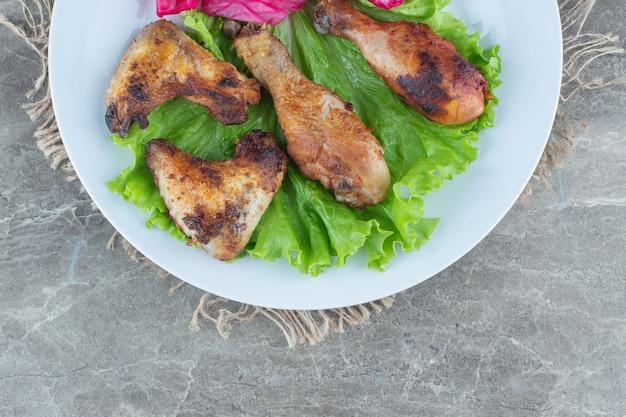 Bovenaanzicht van gegrild kippenvlees met slablaadjes.