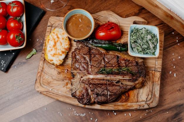 Bovenaanzicht van gegrilde biefstuk geserveerd met groenten en saus op een houten bord